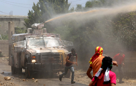 Palestinian protesters throw stones at an Israeli military vehicle spraying a foul-smelling spray known as